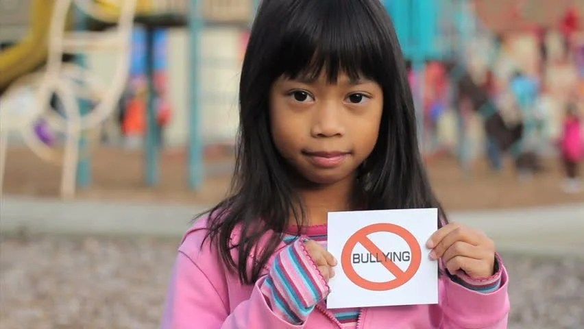 A Cute Asian Girl Holds Up A Small No Bullying Sign On The School Playground