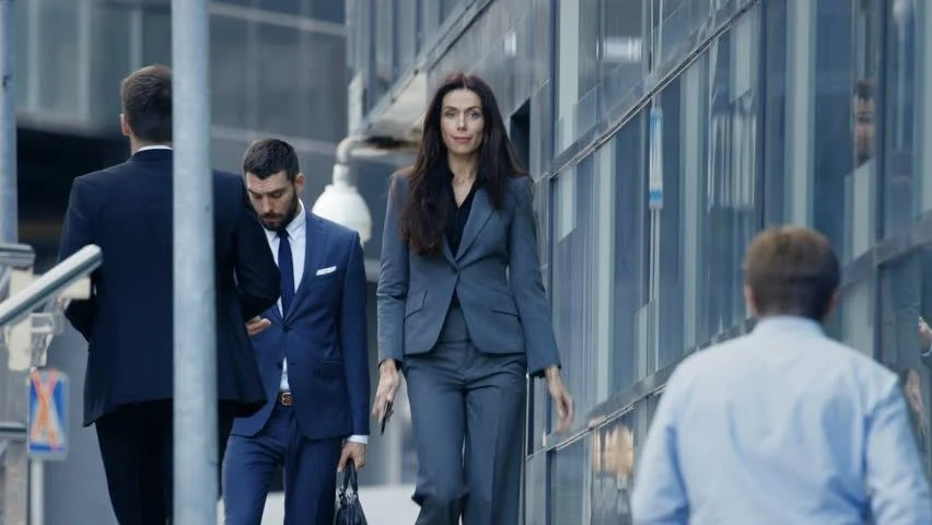 Business Woman And Business Man In Tailored Suits Walk On