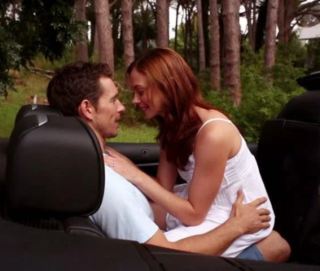 Romantic Couple Making Out In The Back Seat Of Silver Convertible