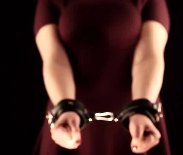 Submissive Woman Wearing A Purple Dress In Handcuffs On Black Background