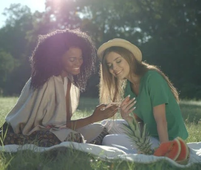 Front View Of Two Young Attractive Multi Ethnic Girlfriends Smiling And Watching Something On The Mobile Phone Suring Their Outdoor Picnic