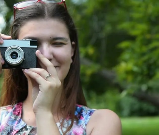 Happy Brunette Teen Girl Taking Picture With Retro Camera