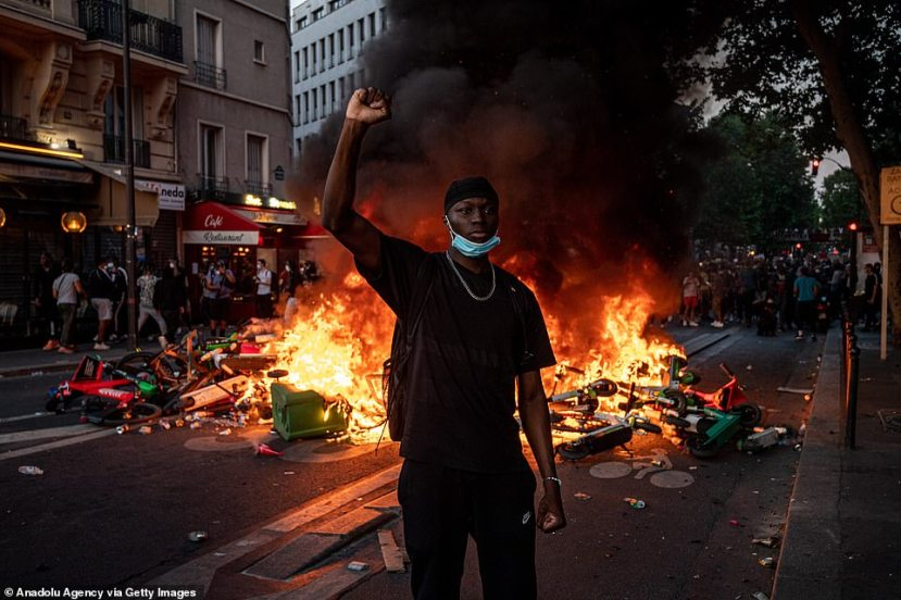 A demonstrator raises his fists in front of a burning barricade as thousands flocked to the Tribunal de Paris courthouse on Tuesday night and clashed with police over the killing ofAdama Traore, a 24-year-old black Frenchman of Malian origin who died in July 2016 after three officers pinned him down with their combined bodyweight