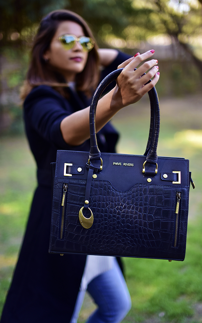 Winter Essentials | Akanksha Redhu | holding out bag in focus