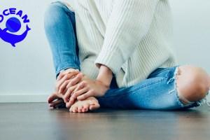 床に膝をたて足首をつかむ女性