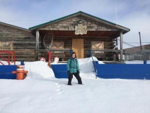 person in front of a cabin in winter