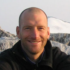 a man smiles in front of a glacier