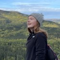 megan pittas in front of a forested mountain