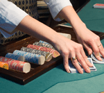 Lady croupier shuffling cards at a poker table