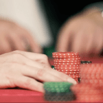 Placing chips at poker table with dealer hand
