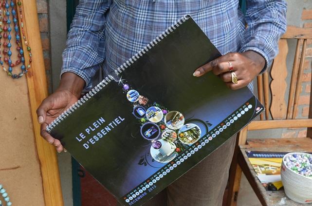 Calénie Nikundanya montrant un calendrier, véritable matière première pour son travail.(www.akeza.net)
