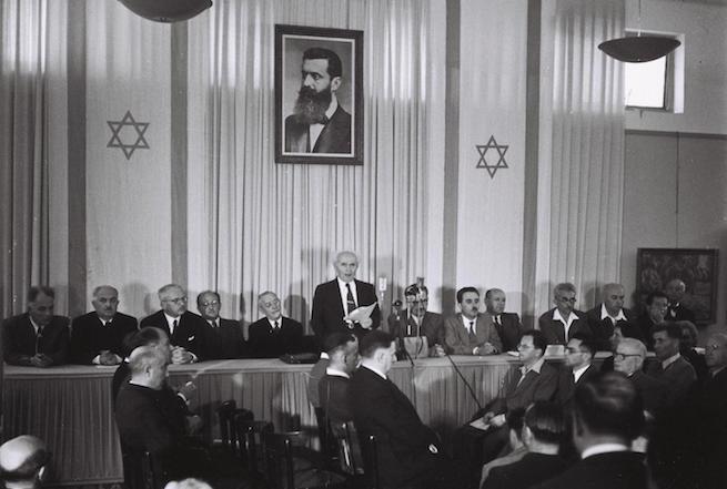 Ben-Gurion bejelenti Izrael Állam függetlenségét, két oldalt a cionista mozgalom zászlója látható