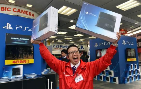 Vendedor japonés mostrando eufórico dos cajas de PS4