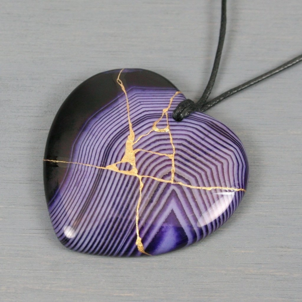 Purple banded agate broken heart pendant with kintsugi repair on black cotton cord