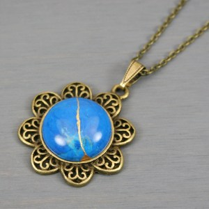 Turquoise howlite kintsugi pendant in antiqued brass setting on chain