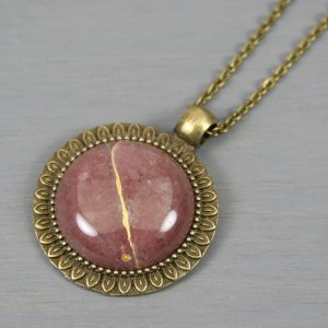 Strawberry quartz kintsugi pendant in antiqued brass setting on chain