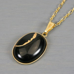 Black onyx oval kintsugi pendant in a gold setting on chain