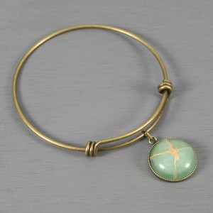 Green aventurine kintsugi charm on an antiqued brass bangle bracelet