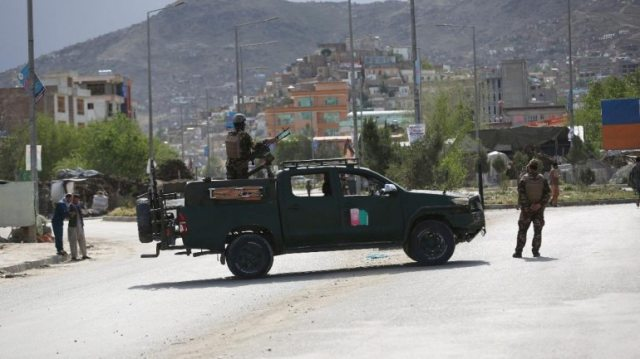 Afghan security forces inspect site of a bomb explosion in Kabul on May 18