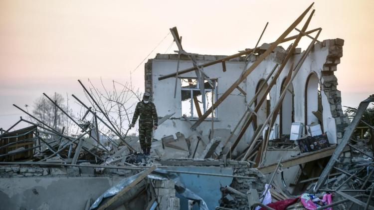An Azerbaijani soldier walking among the debris of destroyed houses in a residential area in Azerbaijan's Ganja city