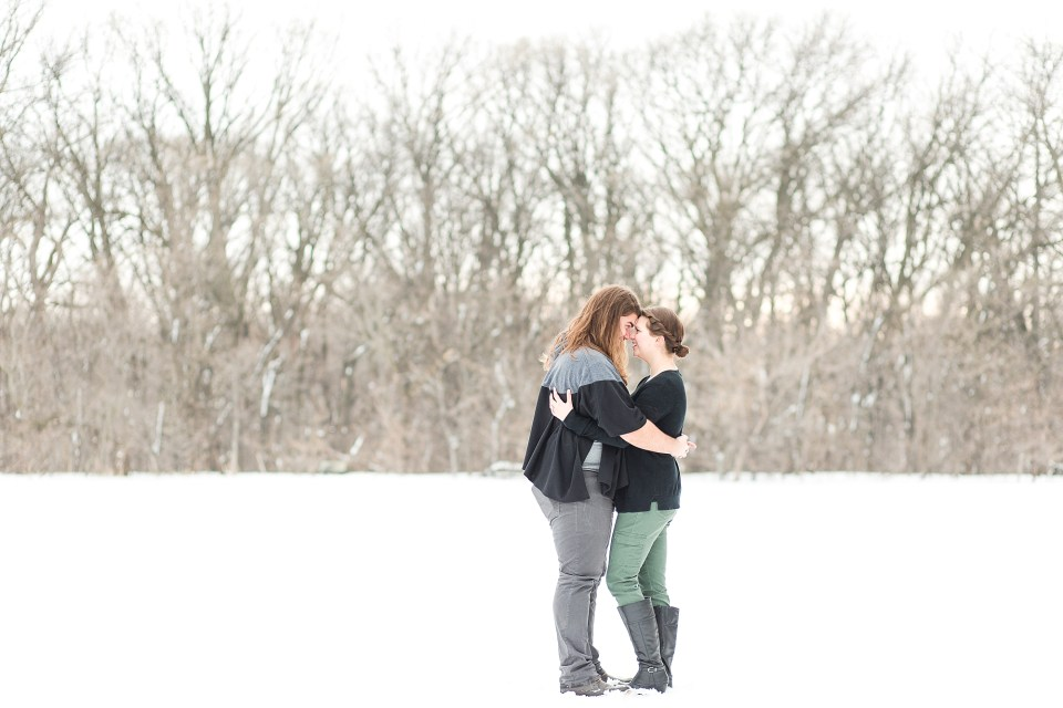 Smiling engagement photos in winter wonderland at Johnson park in Moorhead, MN