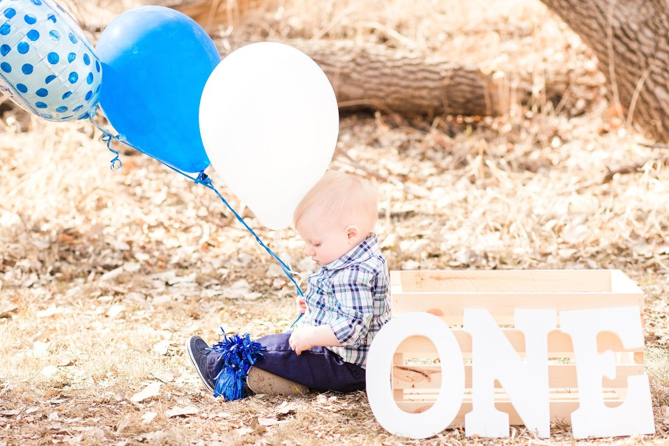 A boy in blue plaid sits in the grass with blue balloons and the word one for his First Birthday