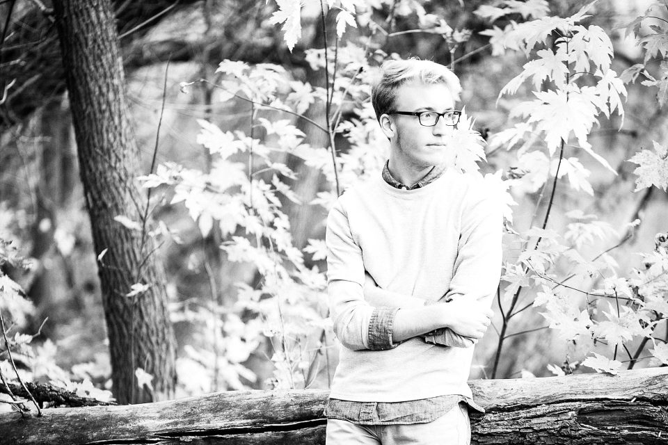 High School Senior in black and white leans against a tree in Fargo, ND Park