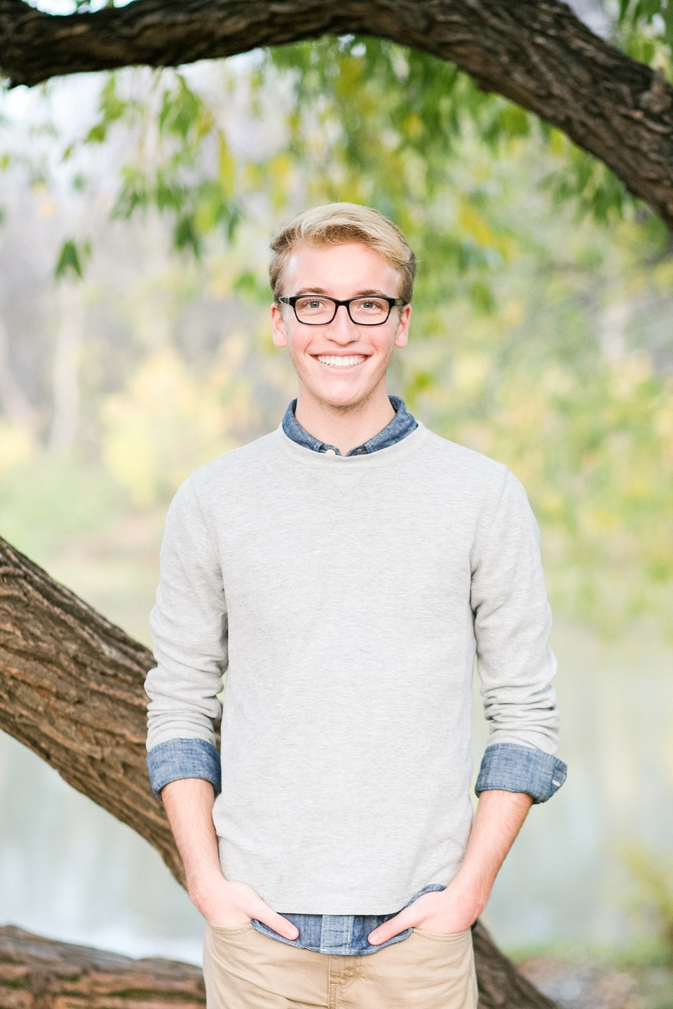 Senior guy smiles in front of the Red River, a tree, and green and yellow leaves in Fargo, ND