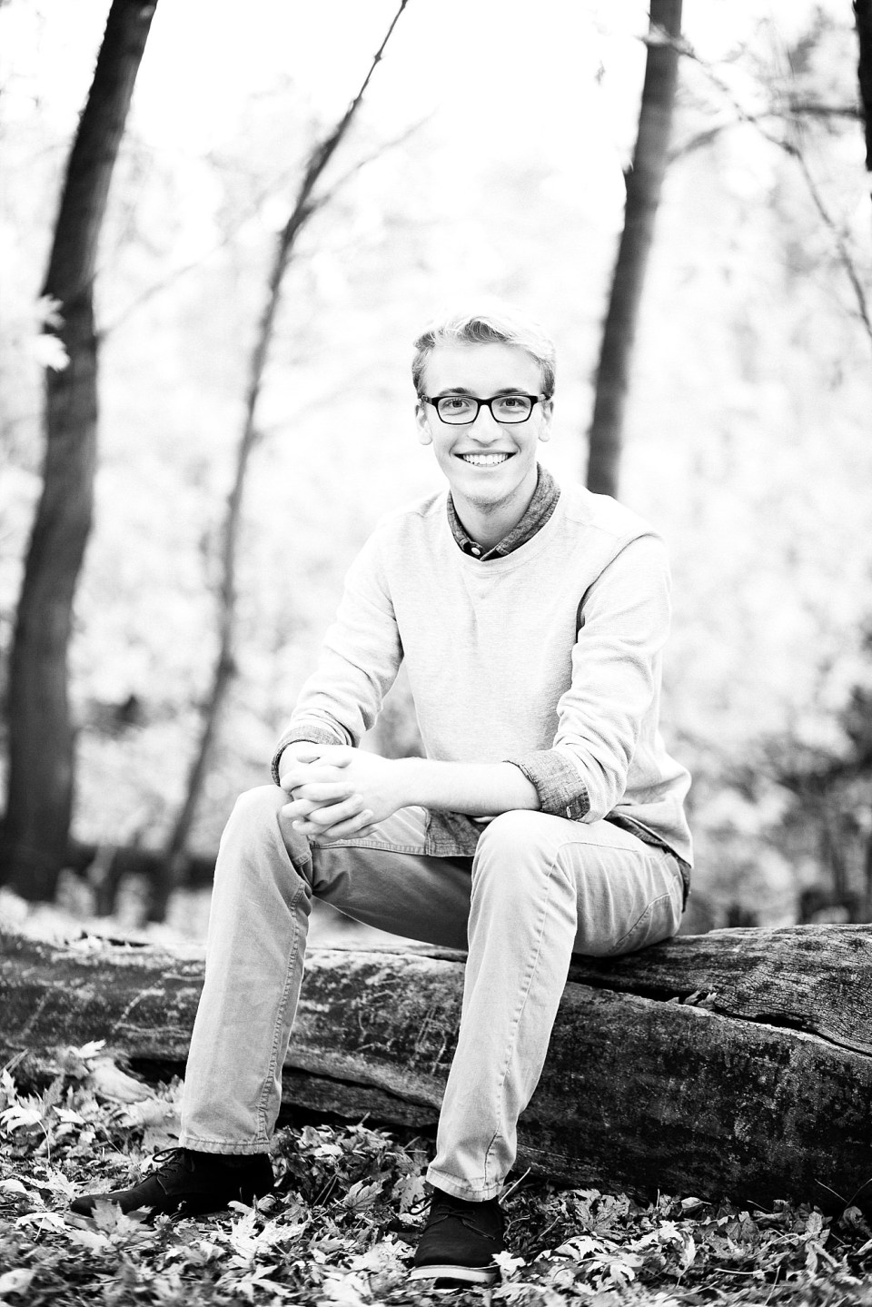 Senior in black and white sits on a tree in his grey sweater and black glasses