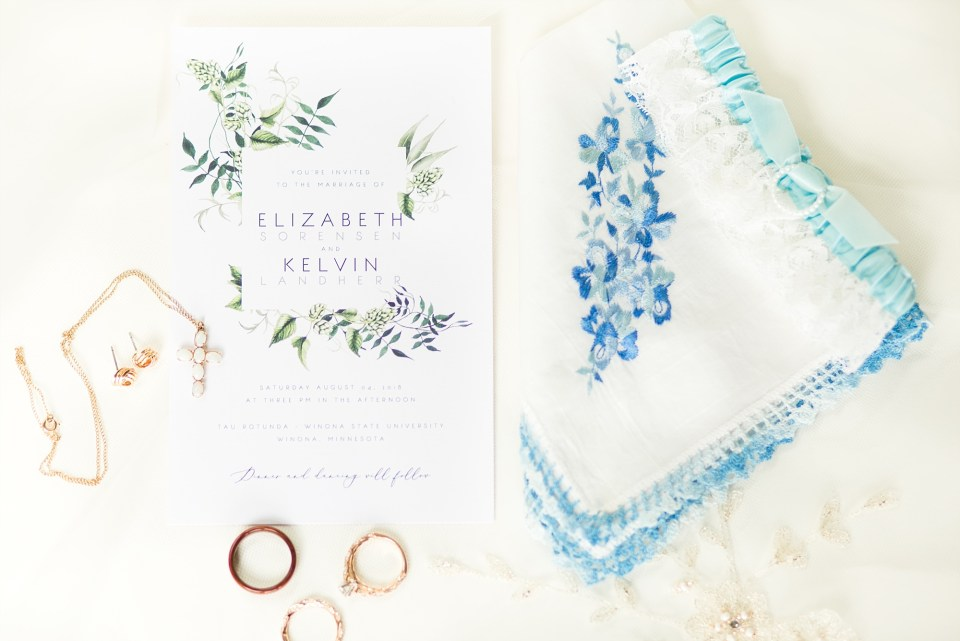 Wedding detail flatlay with blues, greens, and rose gold