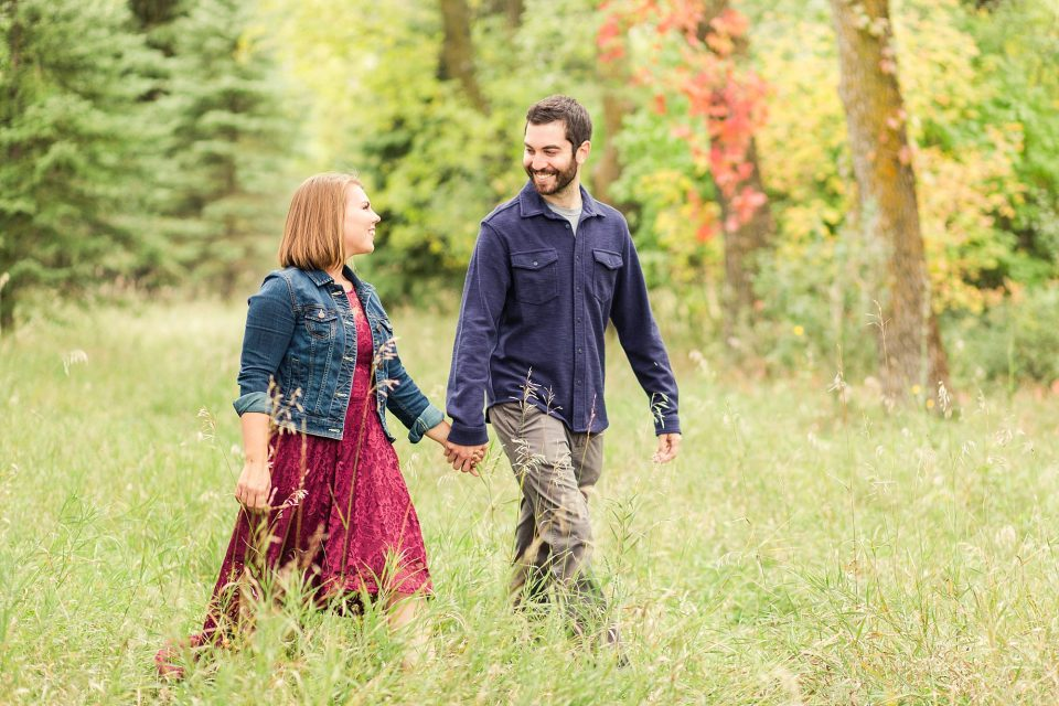 Engaged couple hold hands and walk through the tall grass at Riverwood Park