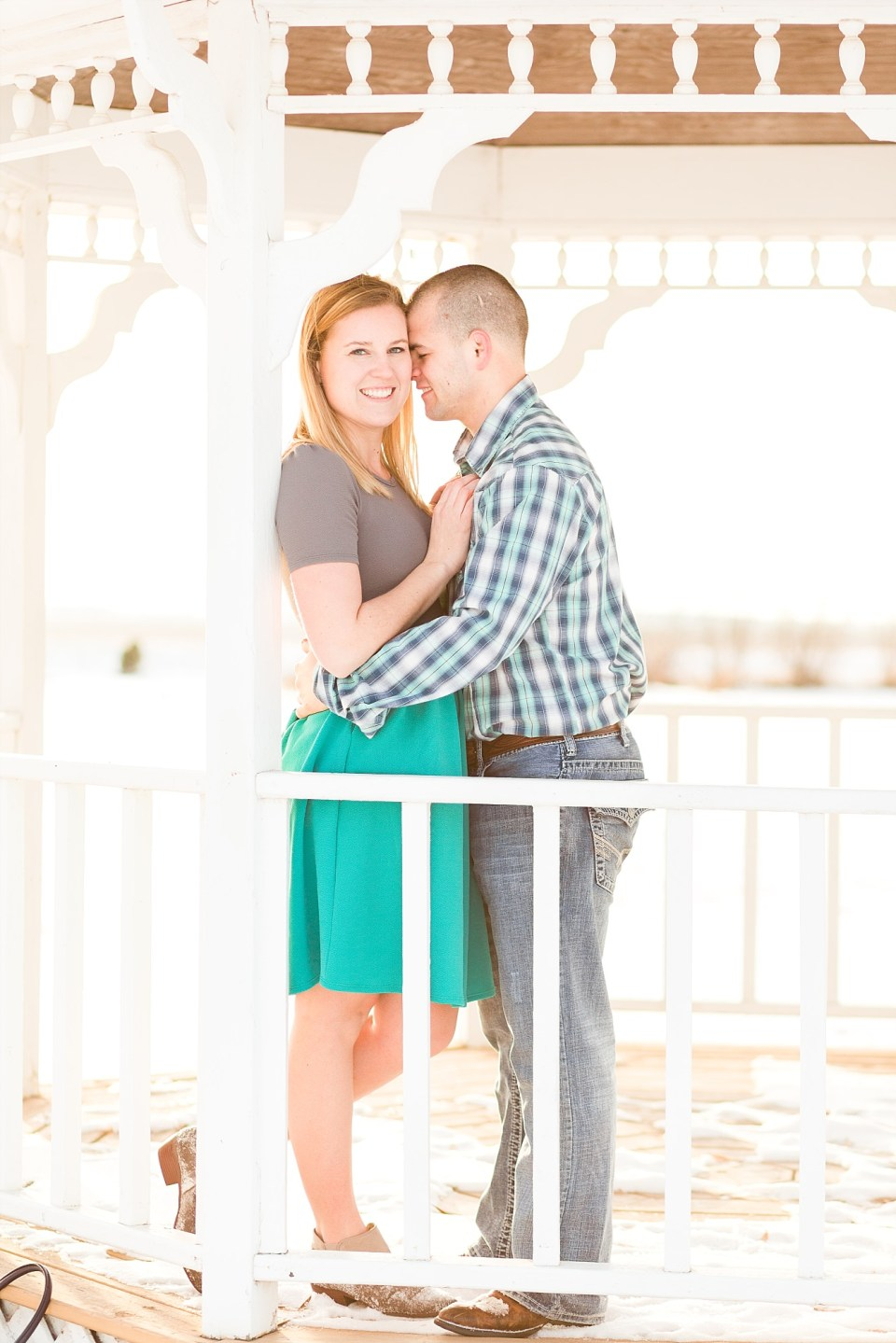 Engaged couple smile under a white gazebo at A Friend's House