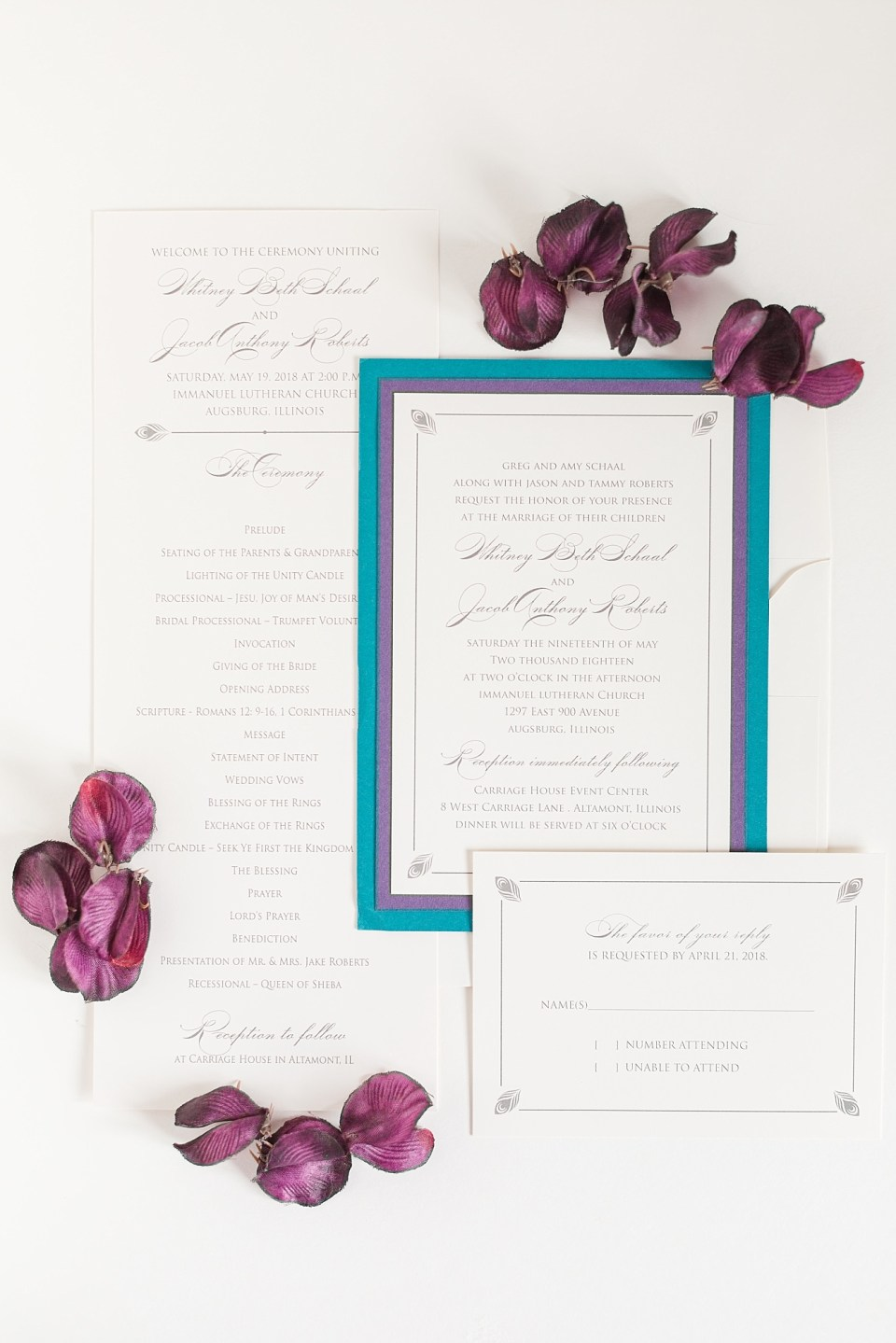 White wedding invites with purple and blue edging and peacock feather details