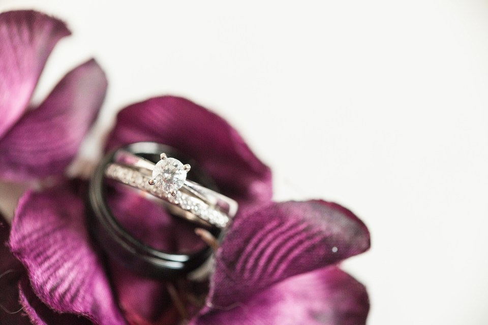 White gold wedding ring set sits on a bed of purple flower petals