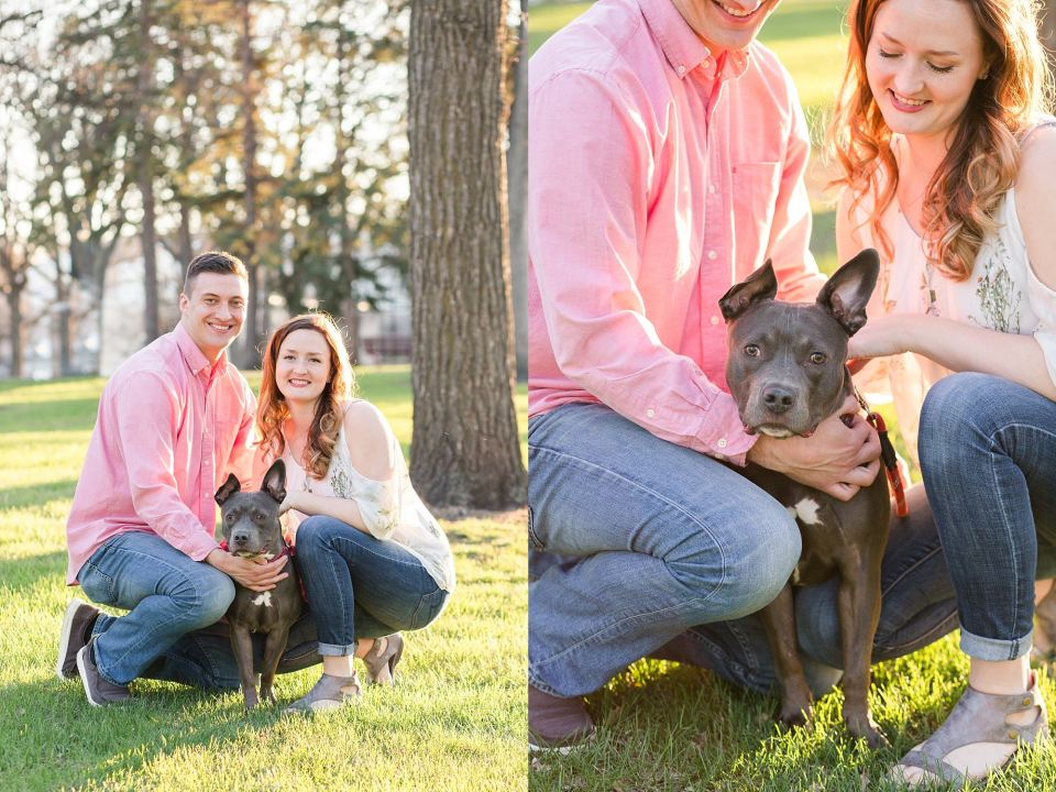 An engaged couple smile with their young pit bull puppy