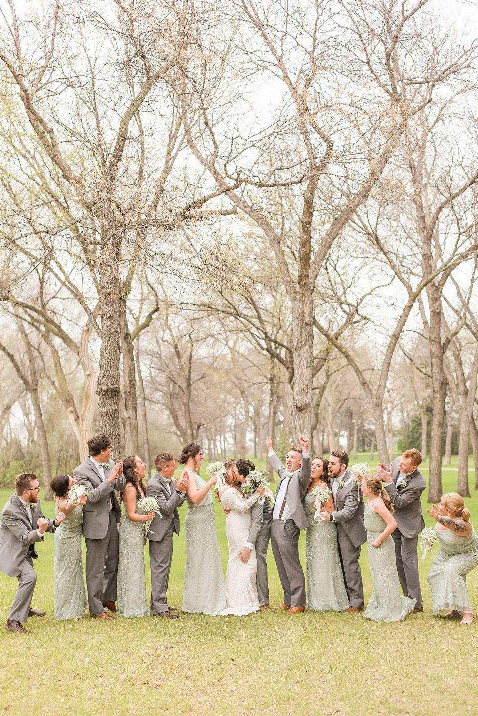 A wedding party in sea-foam green and grey cheer for the newlyweds