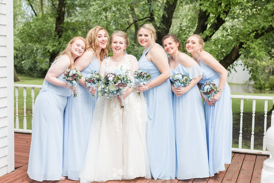 Bridesmaids in light blue surround a bride in a lace dress