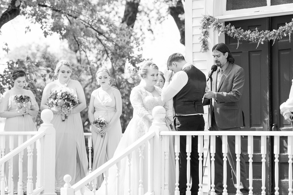 A groom wipes away a tear during an outdoor ceremony in front of a small church