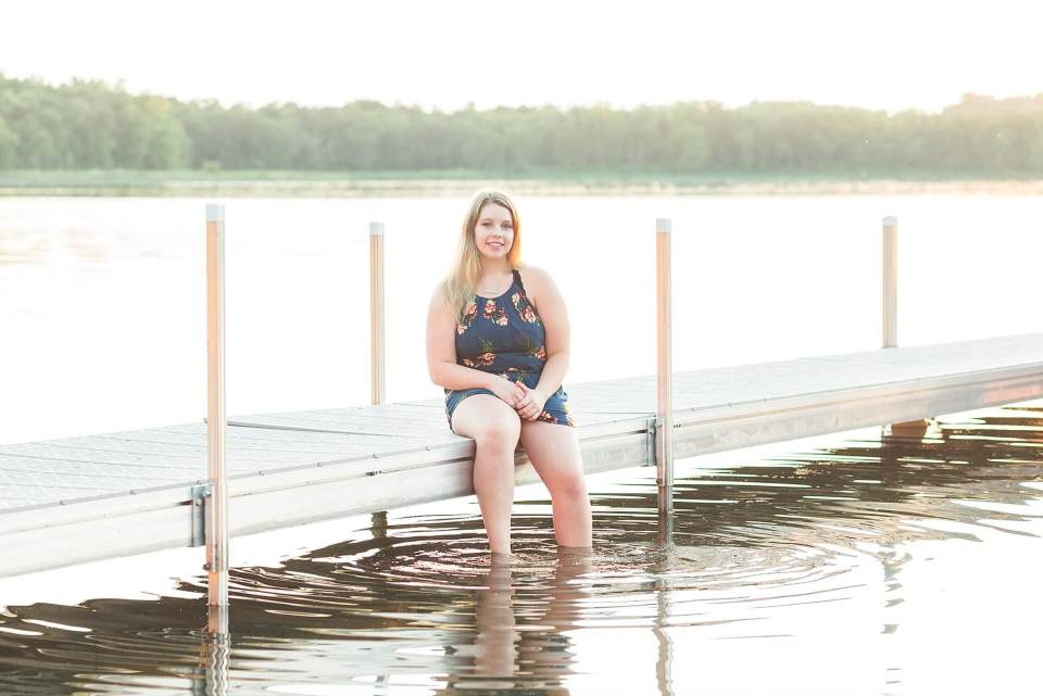 A high school senior dips her feet in the water during her Lakeside Senior Portrait Session