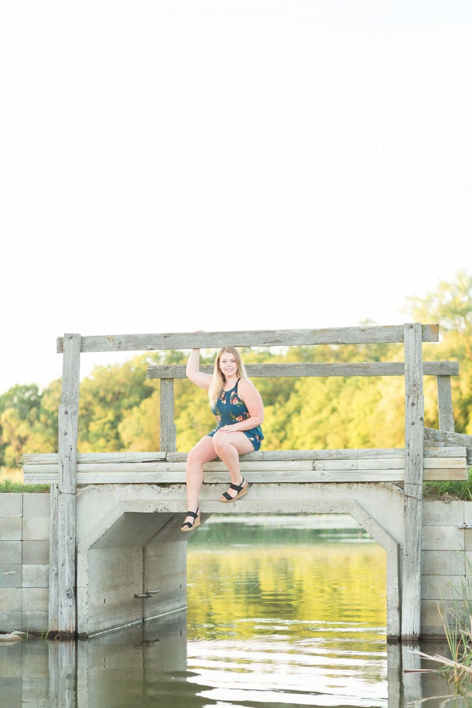 A High school senior sits on a wooden bridge over a lake for her senior portrait session
