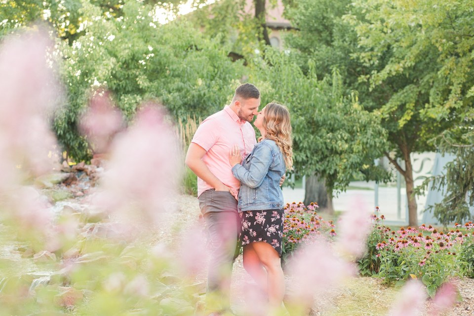 Engaged couple in pink, denim, and floral print kiss among pink and purple flowers
