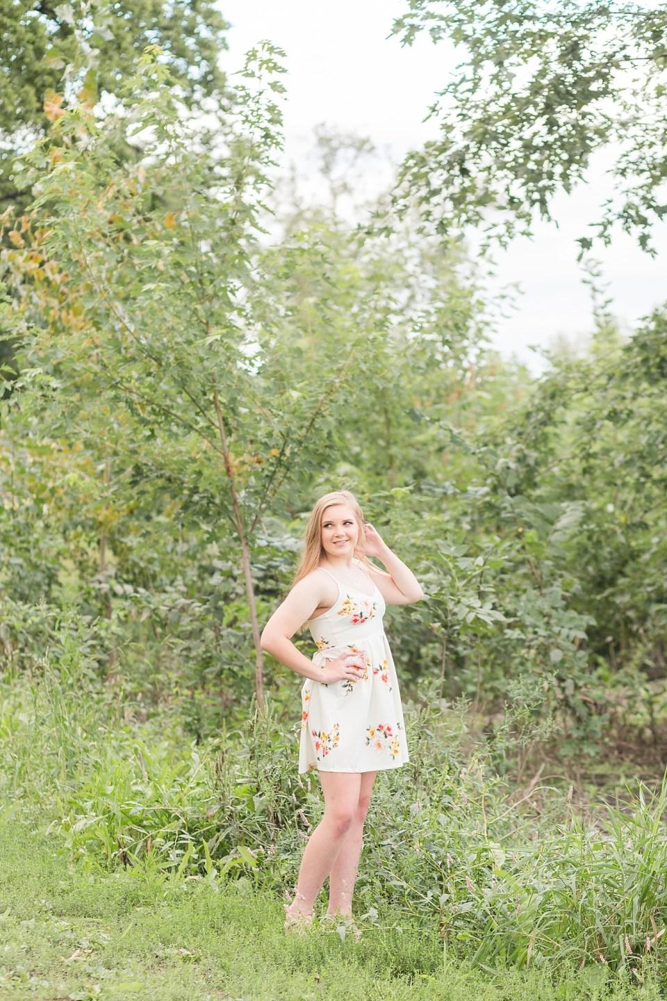 Senior girl looks over her shoulder in tall grass during her Senior Portraits in Fargo
