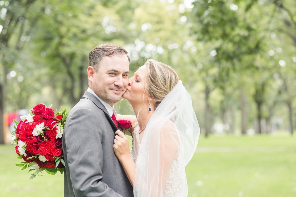 A bride with a long veil leans in to kiss her groom on the cheek in Island Park