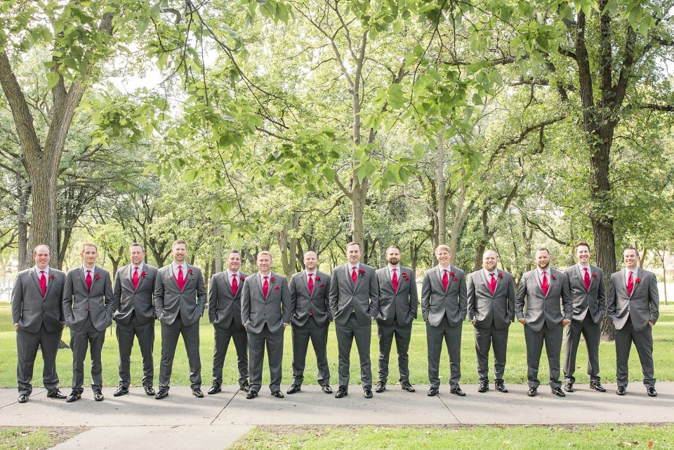 A large group of groomsmen with grey suits and red ties