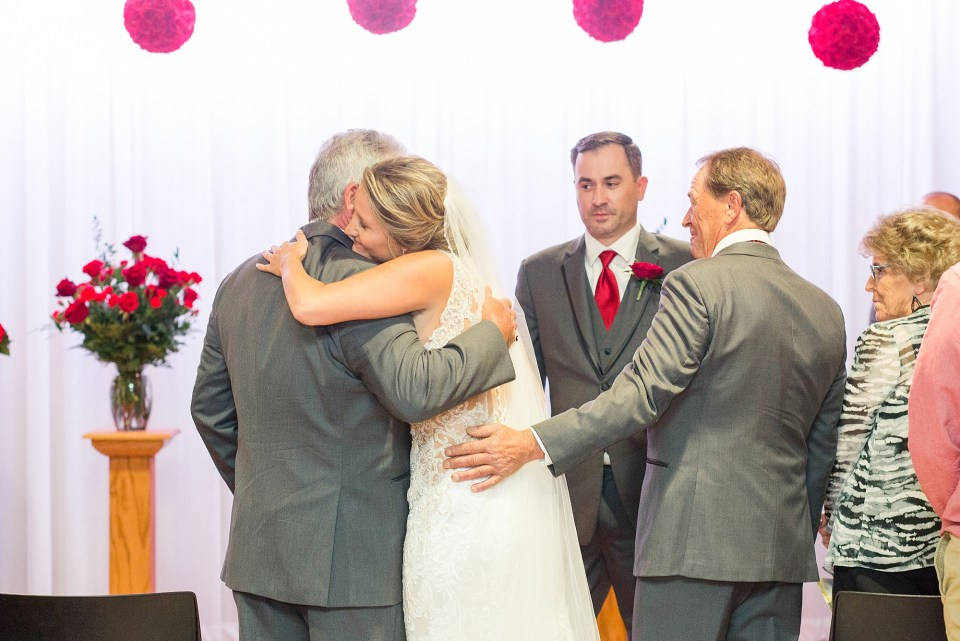 A bride hugs her two father's during her Glamorous Wedding at the Avalon