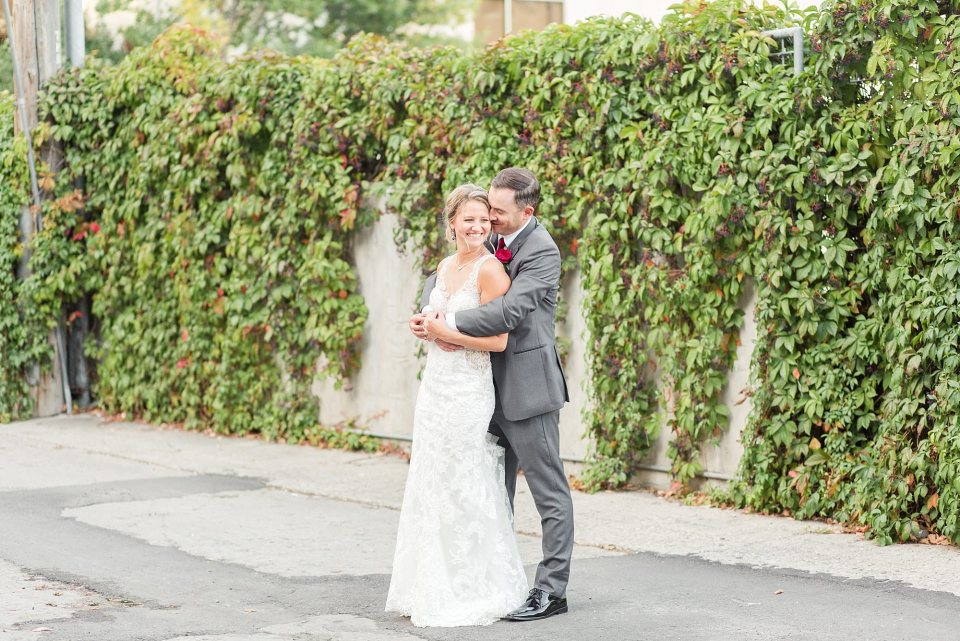 A groom holds his bride tightly near a vine covered wall in Downtown Fargo