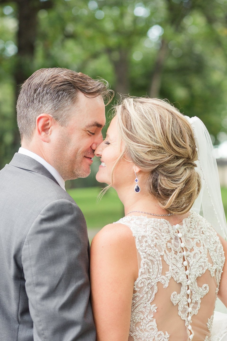 A bride shows off the detailed back of her dress while kissing her groom