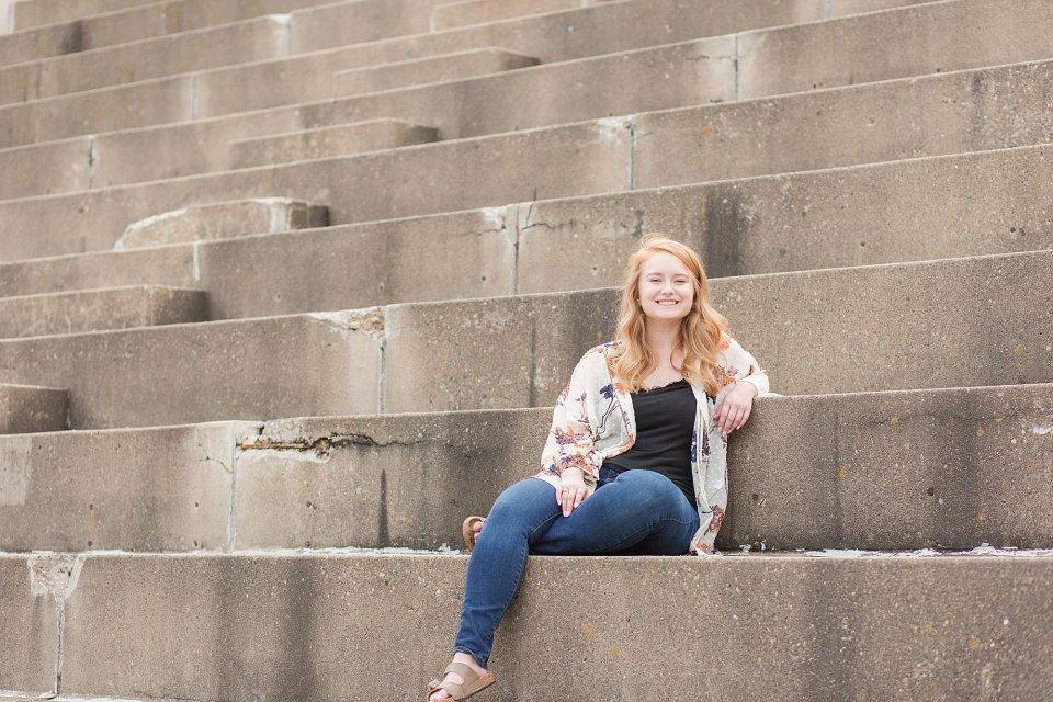 Senior girl leans against cement steps in Island Park
