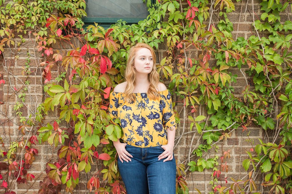 Senior looks off in the distance against fall colors during her Senior Photos in Downtown Fargo
