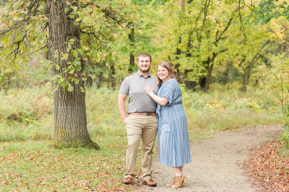 A couple in shades of blue and greys pose in front of the fall colors in Buffalo River State Park